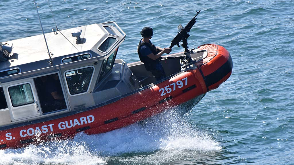 A Coast Guardsman aboard a Coast Guard boat makes a pass near the USS Midway.