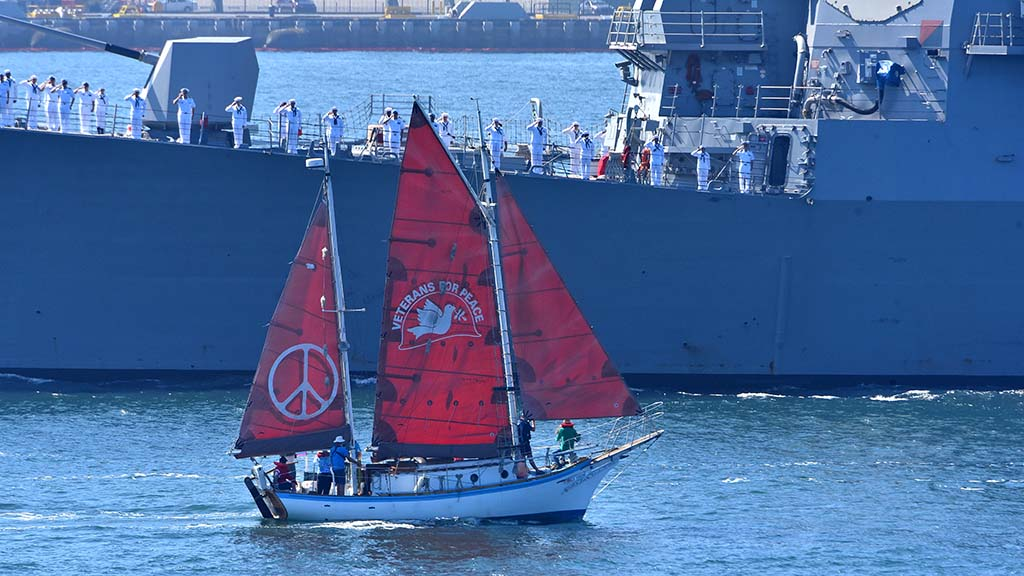 "Members of Veterans For Peace sail their ""peace"" boat, Golden Rule past the USS Spruance in the Sea & Air Parade."