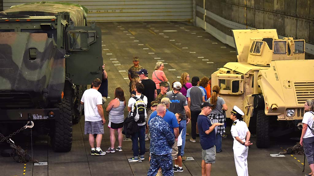 Visitors look at military vehicles in the vast indoor space of the USS Anchorage.