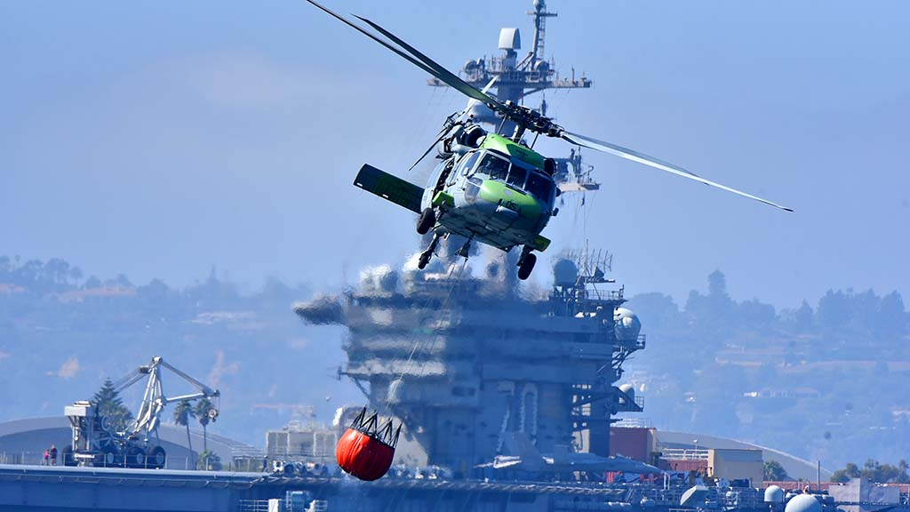 A Navy helicopter carries a container of water as it flies in front of the USS Carl Vinson during the Fleet Week Sea & Air Parade.
