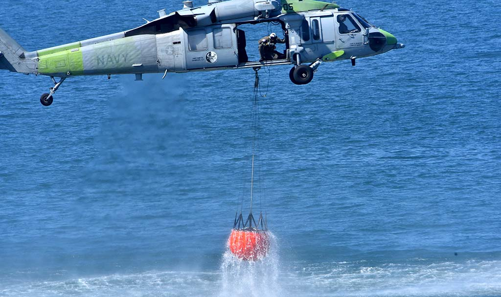 A Navy helicopter crew demonstrate a water drop.