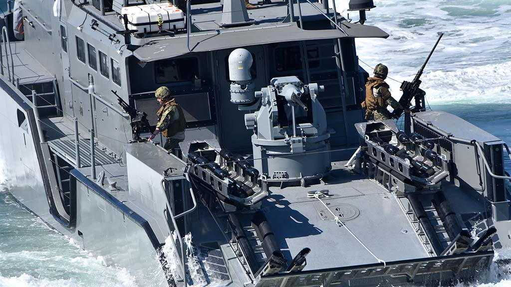 Military personnel aboard a 1250 MK VI patrol boat man their guns.