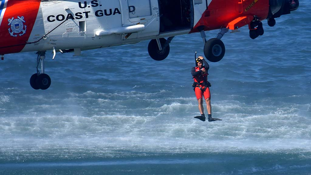 A Coast Guard diver jumps out of a helicopter to demonstrate rescue operations.