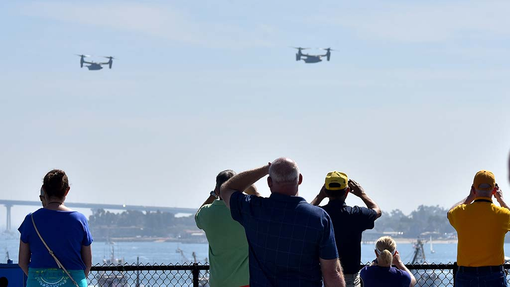 Spectators aboard the USS Midway watch Osprey helicopters in the San Diego Fleet Week Sea & Air Parade.