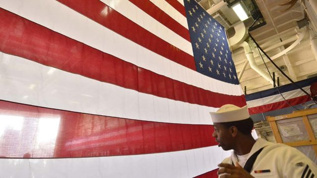 A sailor passes behind an American flag on the USS Anchorage.
