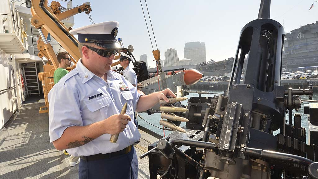 A Coast Guardsman shows the bullets used on the guns on the cutter.