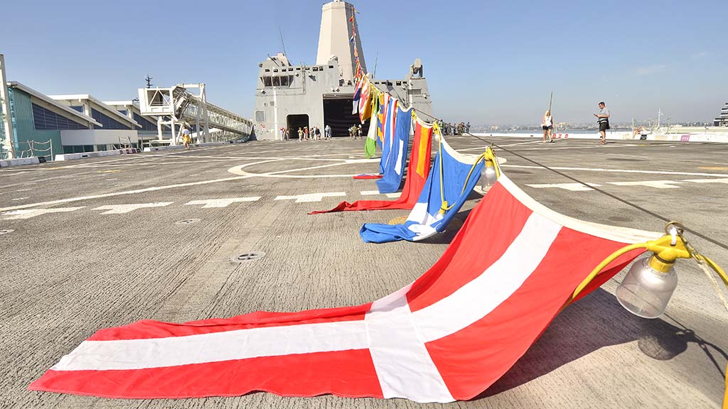 Flags are draped across the deck of the USS Anchorage.