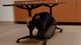 Woman practices taking cover under a desk