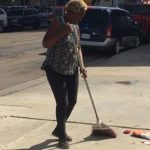 Jeanette Reynolds sweeps up trash in the area where she and her friend stay downtown.