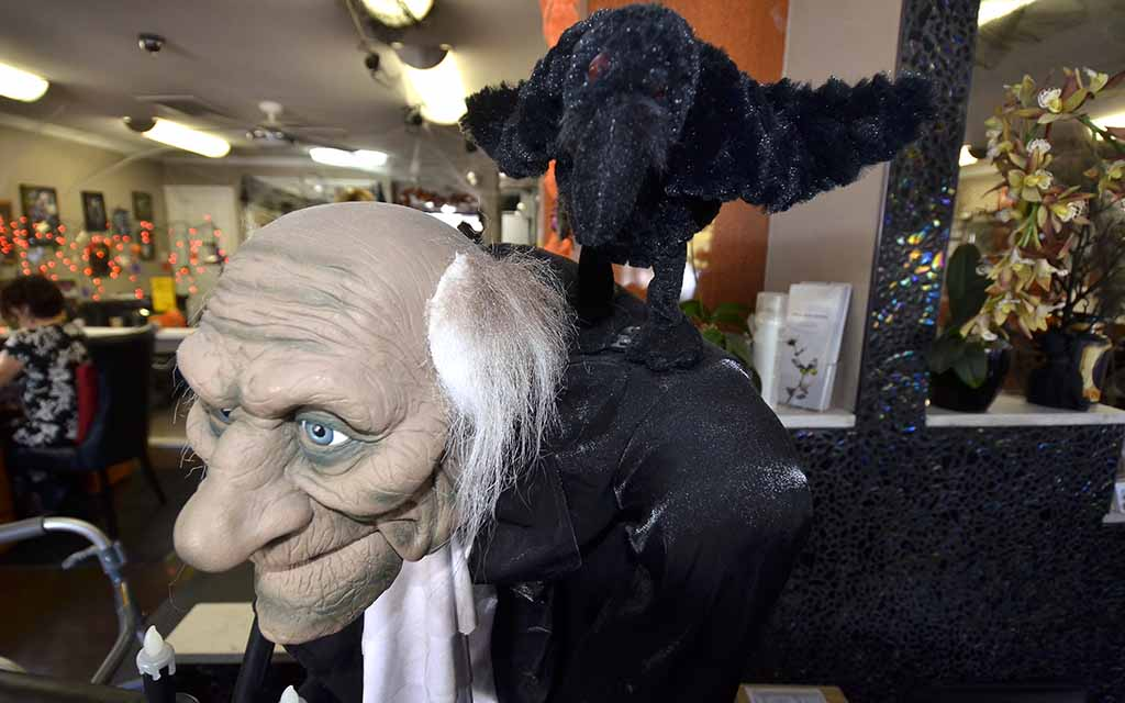 """A raven says """"Nevermore"""" on the shoulder of one of many animated displays at Pizazz Hair and Nail Salon."""
