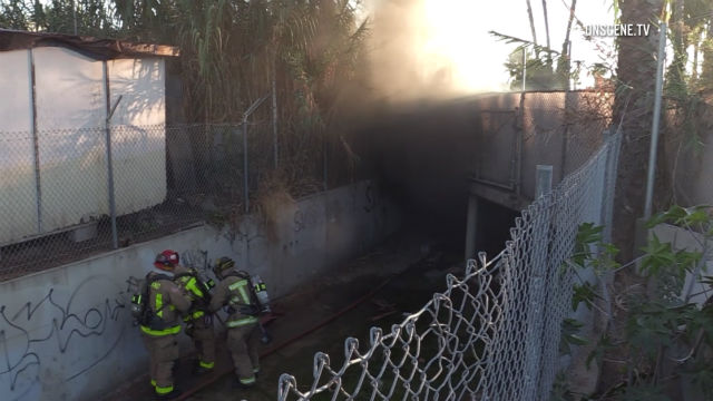 Firefighters outside storm drain