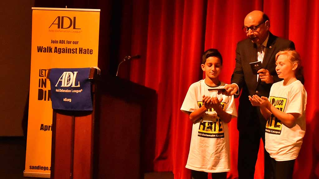 Khizr Khan reverently places U.S. Constitutions in the hands of two local middle-schoolers.