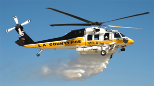 A Los Angeles County Fire Department Sikorsky S70i Firehawk helicopter makes a water drop.