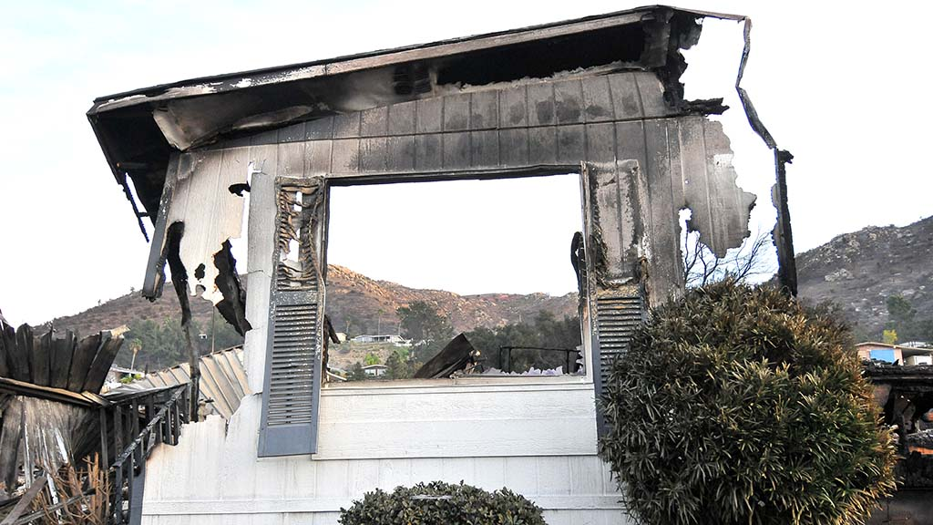 A burned mobile home provides a frame for the foothills in the background at the Rancho Monserate Country Club