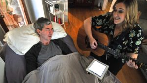 Seasons Hospice & Palliative Care's music therapist Christine Gallagher sings with client Glynne Pisapia.
