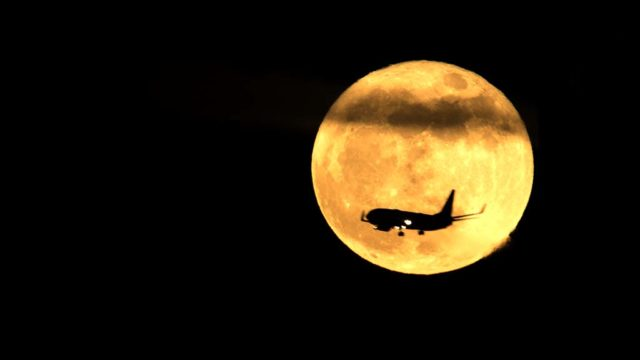 An airplane bound for Lindbergh Field passes in front of the last supermoon of 2017 in downtown San Diego.