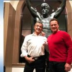 Sylvester Stallone with Arnold Schwarzenegger in front of recently auctioned Rocky statue.