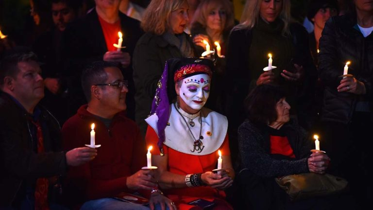Sister Ida of the Sisters of Perpetual Indulgence charity is surrounded by fellow participants at the World AIDS Day remembrance.