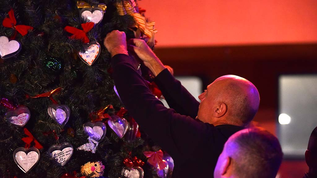A man adds an ornament to the Tree of Life for the World AIDS Day ceremony.