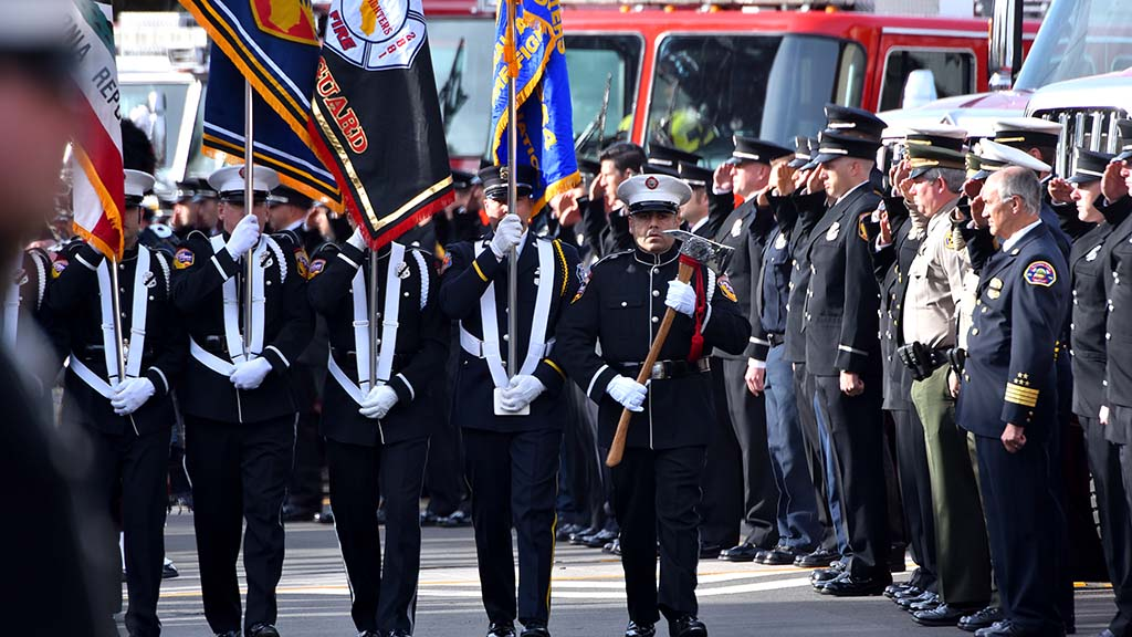 An honor guard proceeds toward San Diego's Rock Church as fire and police officials salute.