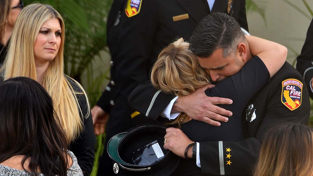 Ashley Iverson comforts Cal Fire Capt. Tim Askins after memorial service at San Diego's Rock Church for her husband, Cal Fire Engineer Cory Iverson.