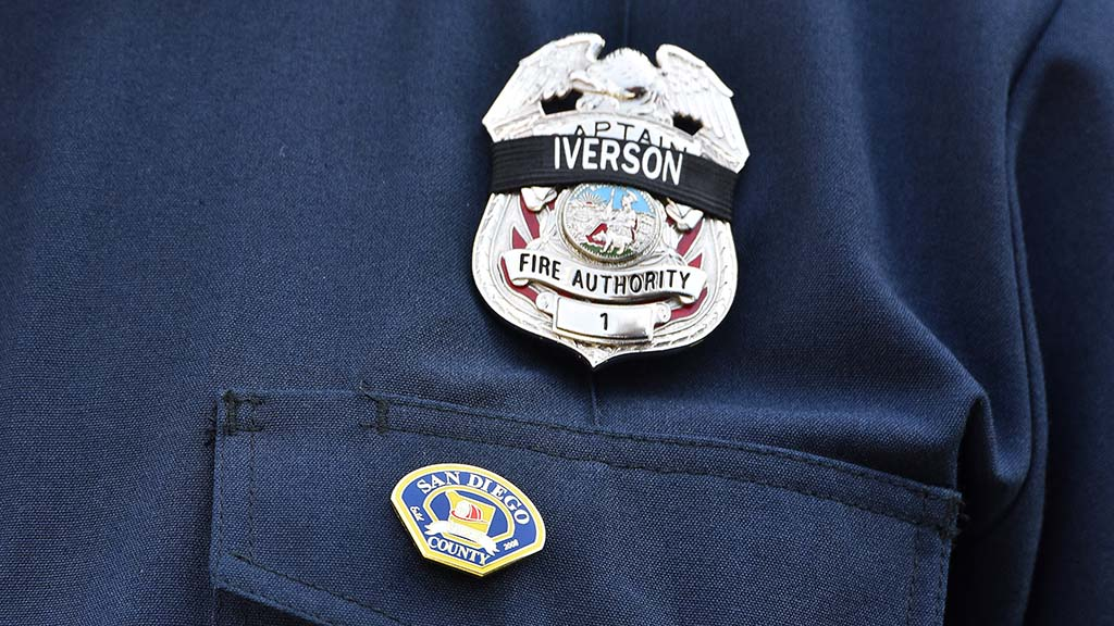 Fellow firefighters wear Cory Iverson's name on their badges.