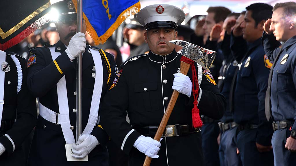 A member of an honor guard proceed to the church for services for Cal Fire Engineer Cory Iverson.