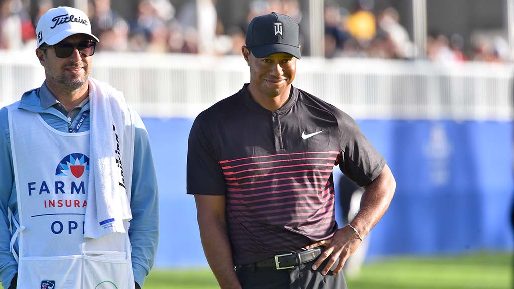 Tiger Woods smiles while standing with a caddie on the South Course.