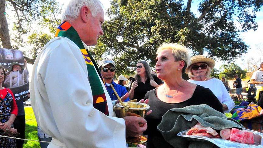 Ellen Ericksen, an animal rights activist, insists that the Rev. Michael Sinor, bless bacon and bones.
