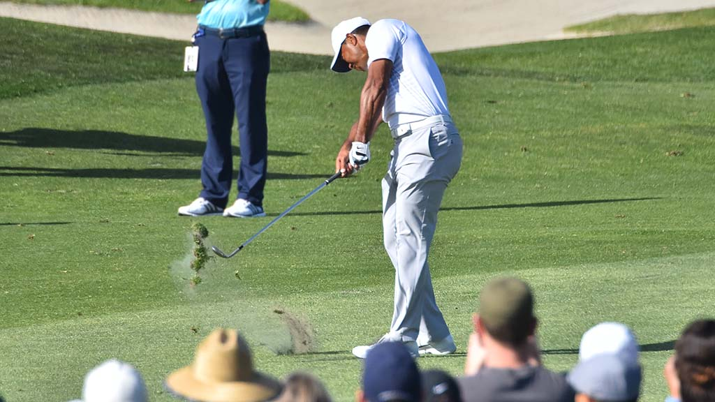 Tiger Woods sends up a divot as he hits down the fairway on Hole #5.