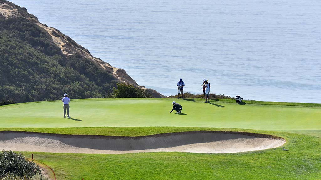 Golfers putt on the green of Hole #3 overlooking the ocean.