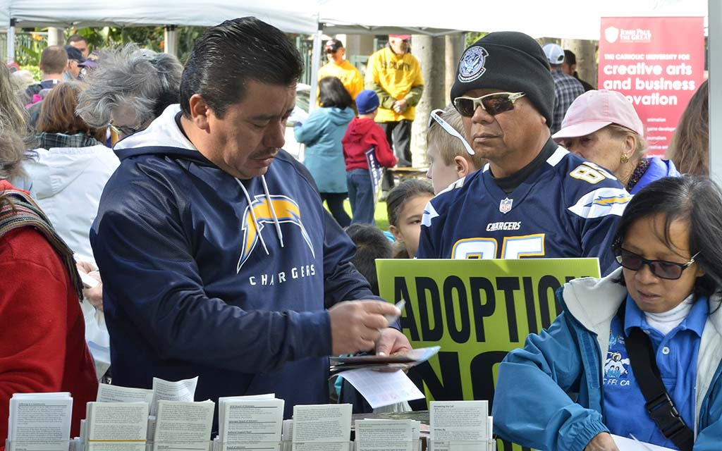 Chargers faithful check out literature at one of four dozen booths.