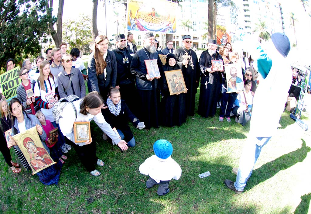 Greek Orthodox priests from around the area gathered for a group shot, with a child not immediately cooperating.