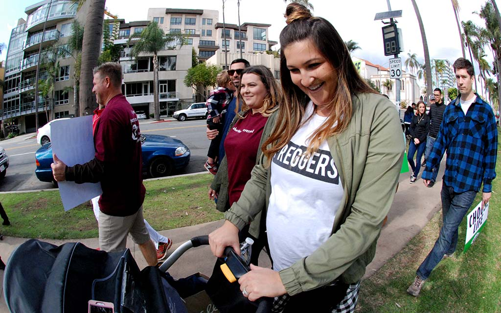 Proudly pregnant marcher pushes a stroller during Walk for Life.