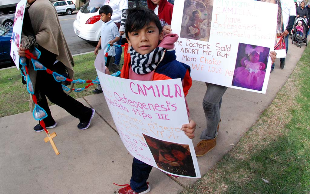 With mom trailing, a child carries poster describing how doctor advised abortion.