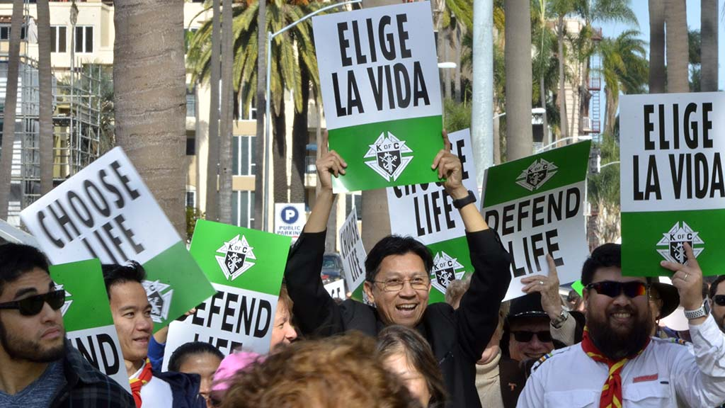 The Rev. Minh Do of Vista's St. Francis of Assisi Parish holds a sign high.