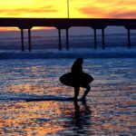 A woman with a skim board walks across the beach of Ocean Beach pier.
