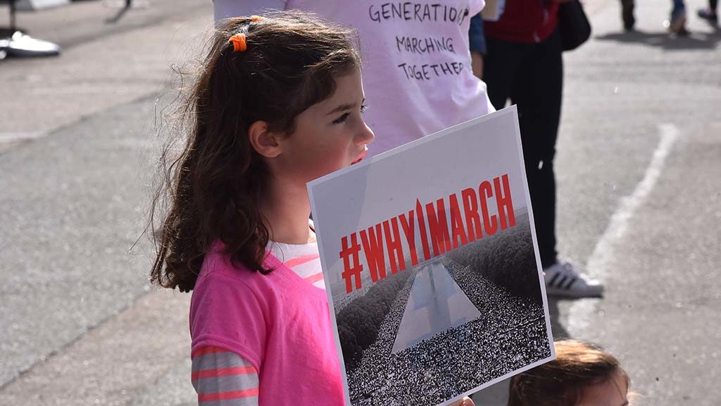 A young girl holds a sign on the side of the road as marchers pass.