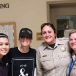 Kaley Cuoco, in ballcap poses with Department of Animal Services staff at her rabbit adoption visit.