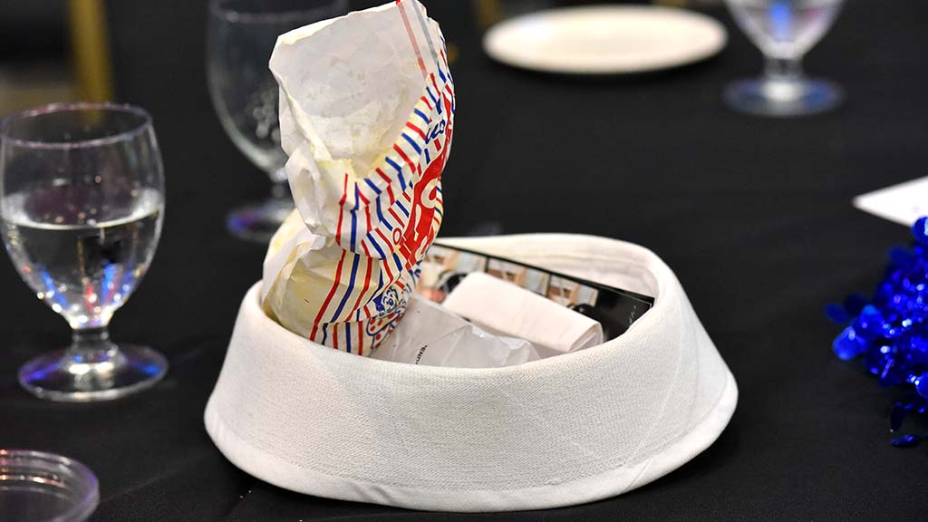A sailor's hat is filled with the fun of the night: popcorn, photos and a gift for his daughter.