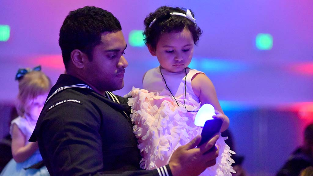 A crew member from the USS John Murtha shares a special moment with his daughter at the YMCA dance.