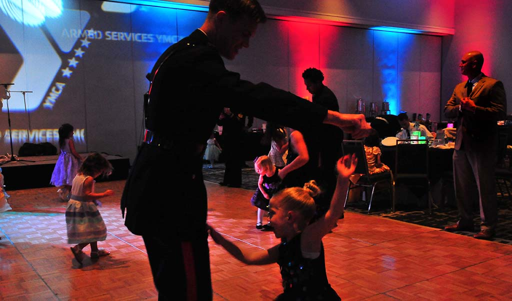 A marine officer dances with his young daughter at the Armed Services YMCA Father & Daughter Dance.