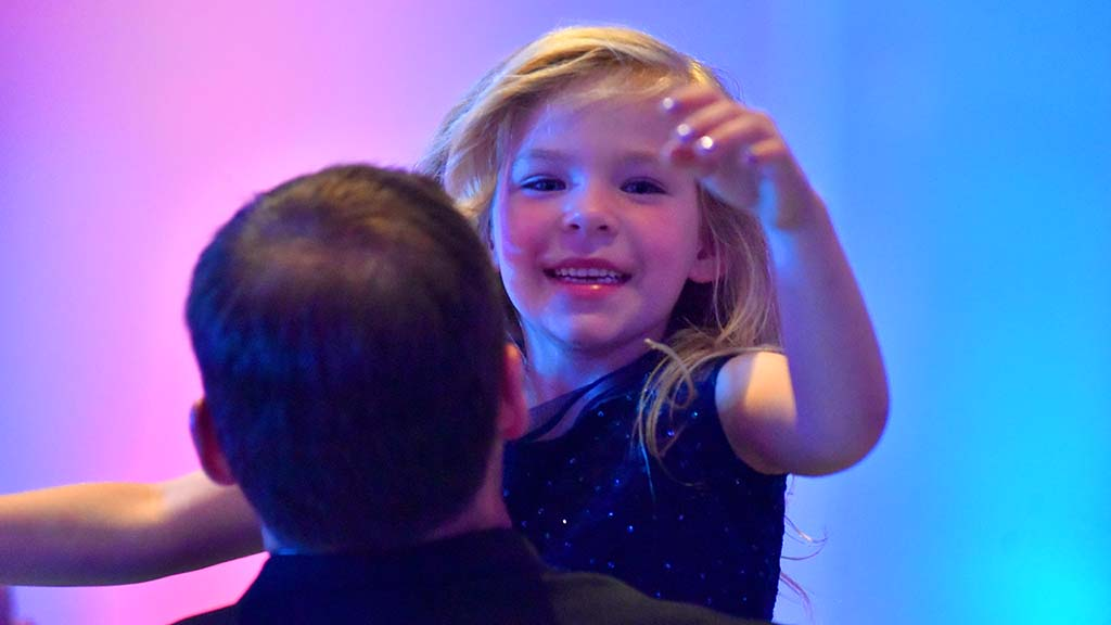 A daughter enjoys a dance with her father at the Armed Services YMCA Father & Daughter Dance.