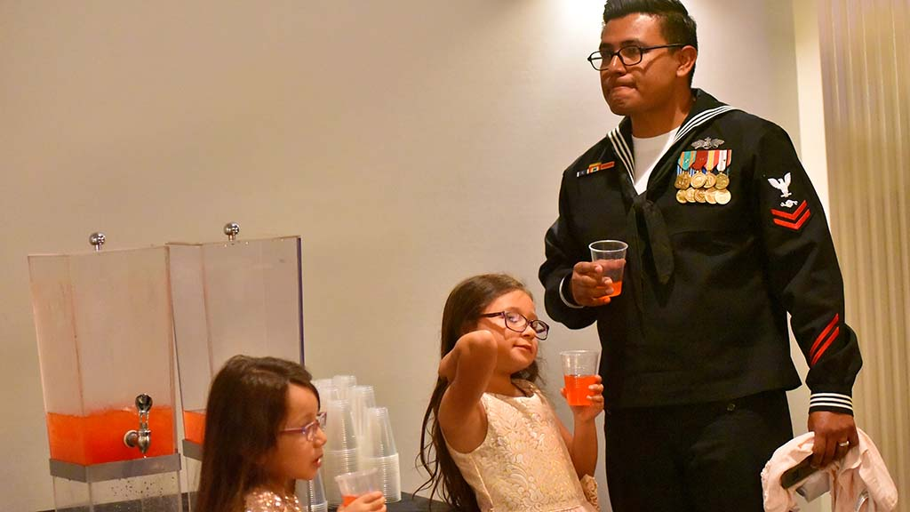 Pedro Cenaperez and his daughters Rose (middle) and Abi enjoy punch before the dance.