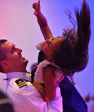 Lt. Com. Brian Deadmon gives his daughter, Jayel, 6, a lift on the dance floor.