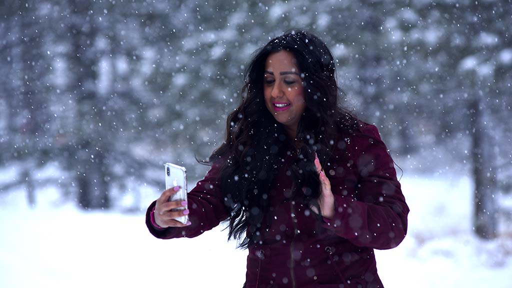 Woman taking selfie in snowball.