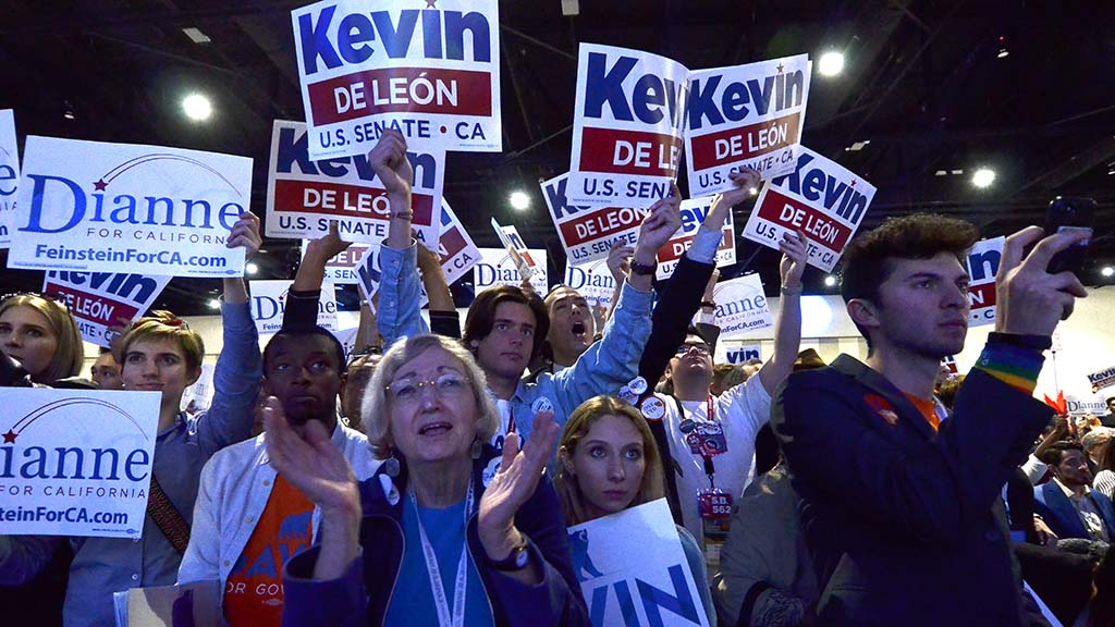 Supporters of senate candidate Kevin De Leon and U.S. Sen. Dianne Feinstein hold up their signs for their candidates.