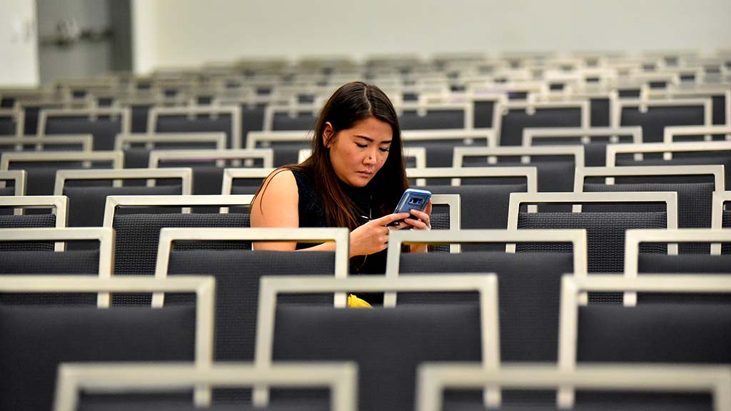 A delegate checks her phone in a cleared out convention meeting room.