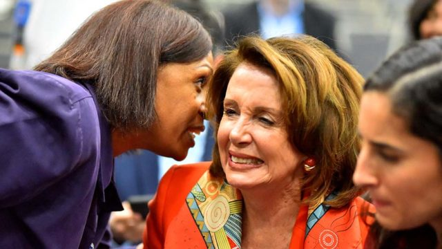 House Minority Leader Nancy Pelosi laughs during a conversation at the women's caucus.