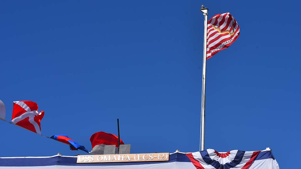 A Don't Tread on Me flag flies next to the name of the ship on the deck.